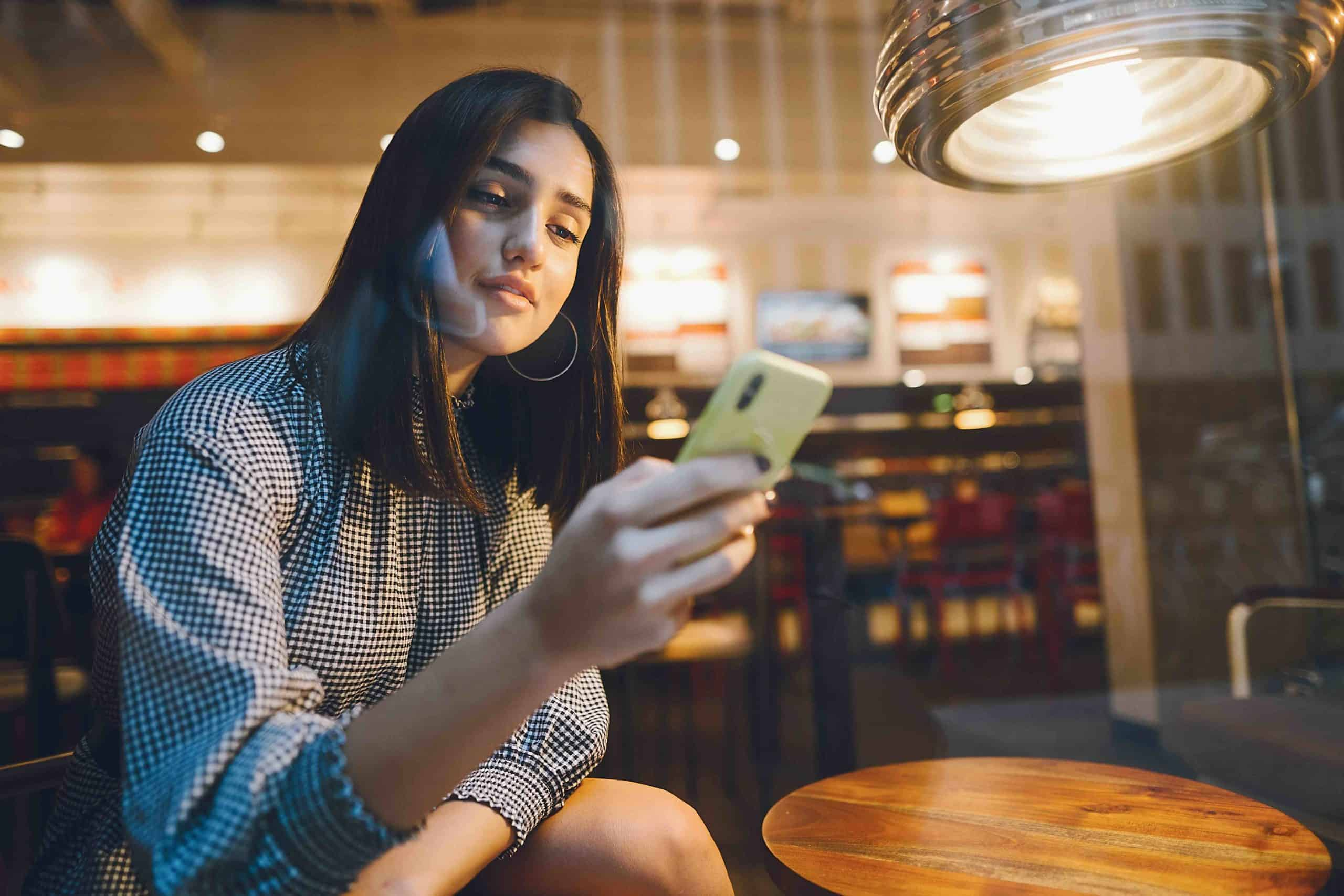 brunette girl using her cellphone to reach a friend